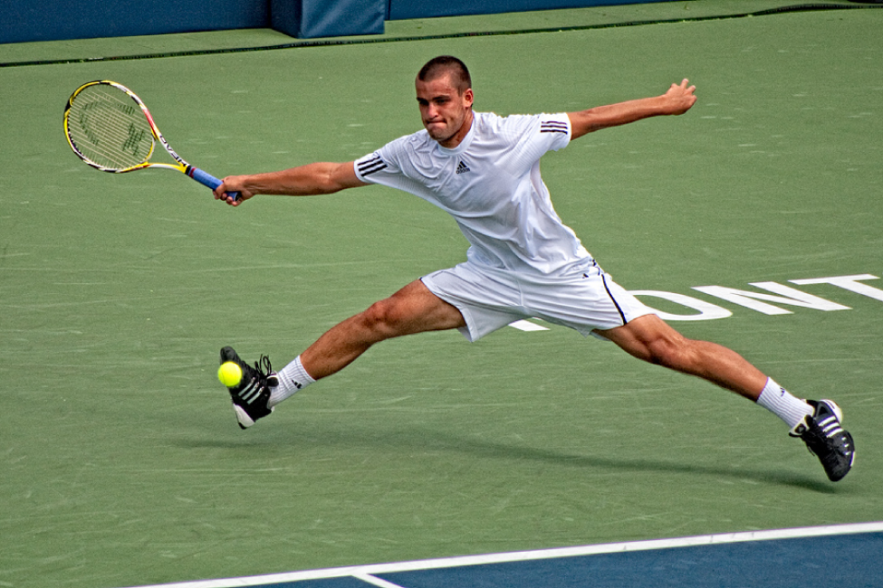 This photograph shows a man playing tennis.