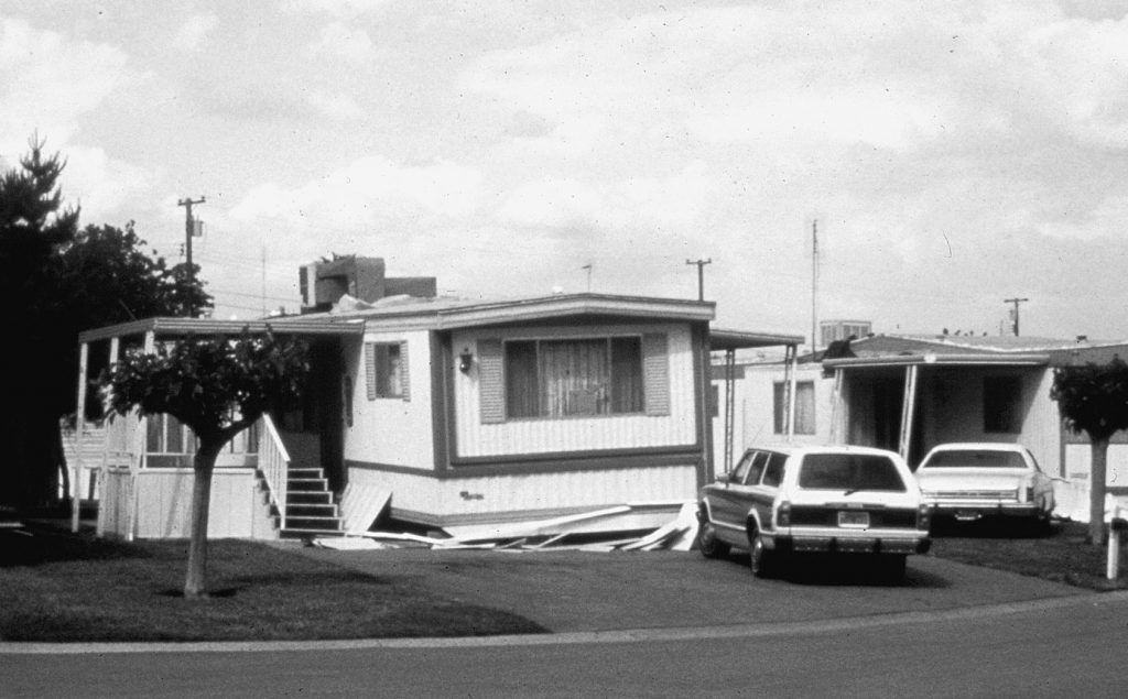 Mobile home has slid off its supports during an earthquake.
